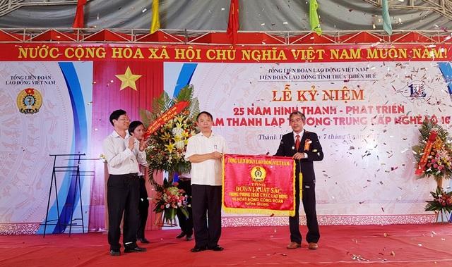 Th.s. Lê Hòa, Hiệu trưởng trường Trung cấp nghề số 10 (bên phải) nhận cờ thi đua của Tổng LĐLĐVN