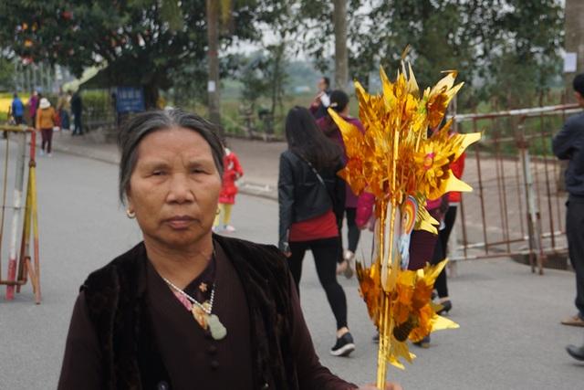 Một người đi cầm hoa đi lễ cầu lộc, cầu tài ở đền Trần