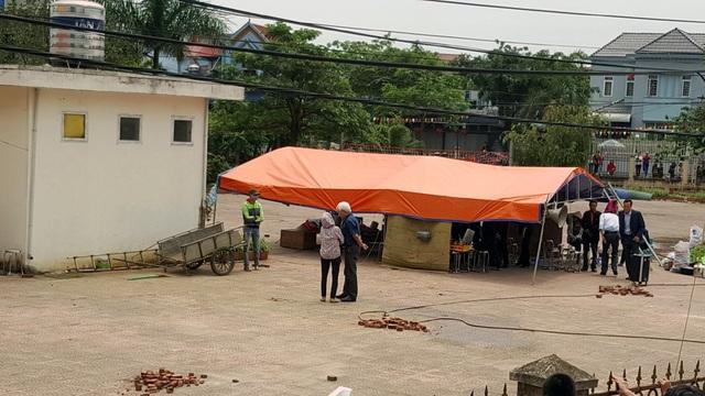 Đoàn công tác và đại diện người dân làm biên bản bàn giao tại lán được dựng trong sân nhà văn hóa. Ông Dương Trung Quốc (áo xanh) cũng có mặt, trò chuyện cùng người dân.