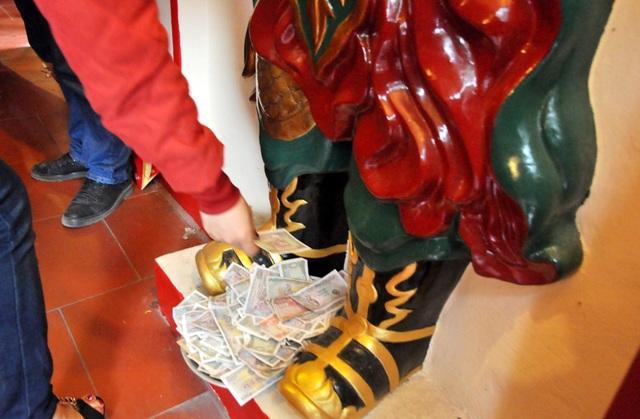 Dưới chân các tượng thờ cũng phủ kín tiền lẻ của người đi lễ