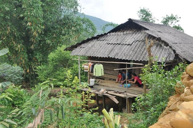Ngôi nhà sắp đổ của bố con em Hồng cheo leo, sau những ụ đất cao.