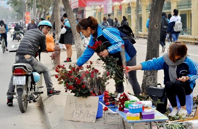 Nhóm bạn sinh viên trường ĐH Thương Mại bày bán hoa và quà ngay trước cổng trường. Với giá bán là 15.000 nghìn đồng/bông, nhóm bạn này nhẩm tính nếu tiêu thụ hết 500 bông hoa đã nhập về thì sẽ thu lãi được khoảng hơn 1 triệu đồng.