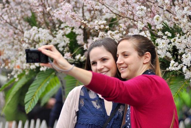 Hai nữ khách nước ngoài tranh thủ ghi lại những khoảnh khắc ấn tượng bên lễ hội hoa
