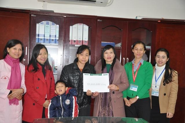Ths.bs Vũ Thị Hồng Phương, trưởng phòng Tổ chức cán bộ, phụ trách phòng Công tác xã hội thay mặt trao quà của bạn đọc Dân trí đến mẹ con chị Nguyên.