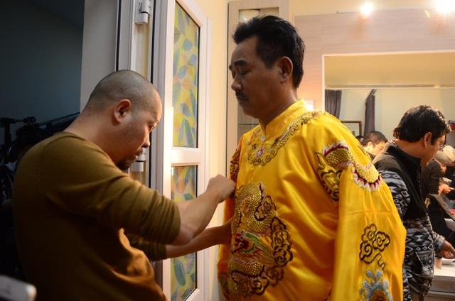 Sau đó anh được nghệ sĩ Xuân Bắc và NTK Đức Hùng giúp chỉnh trang lại y phục và đội mũ.