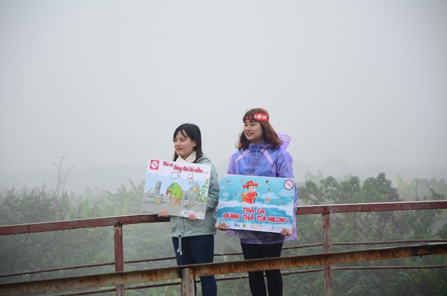Nhiều bạn trẻ tình nguyên đứng rất kiên trì trên cầu, tay cầm thông điệp thuyết phục người dân.