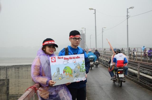 Nhiều bạn trẻ tình nguyện có mặt trên cầu Long Biên để thuyết phục người dân thả cá nhưng không thả túi nilon để giữ vệ sinh môi trường.