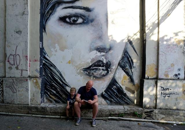 Hai bố con người nước ngoài ngồi đọc sách trước bức hình graffiti do các bạn trẻ sáng tạo.