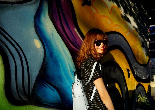 Một bạn nữ tạo dáng bên bức tường nhiều màu sắc trong nhà ga.