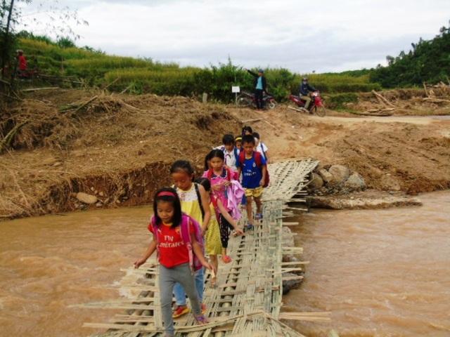 Đường trở lại trường học của nhiều học sinh khó khăn hơn sau cơn lũ. Người dân phải bắc cầu tạm bợ cho các cháu đến trường.