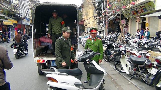 Xe máy để dưới lòng đường bị lực lượng công an đưa về đồn xử lý