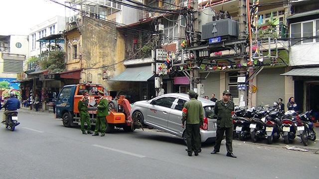 Một chiếc ô tô vô chủ đỗ trái phép dưới lòng đường bị cẩu về đồn.
