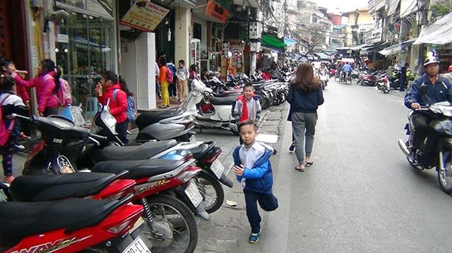 Vỉa hè bị chiếm dụng, buộc các em học sinh phải đi bộ dưới lòng đường