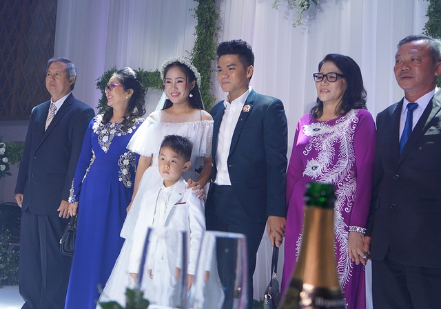 Cặp đôi hạnh phúc trong ngày cưới bên cạnh gia đình và sự chúc phúc của người thân, bạn bè.