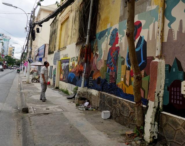 Một người đàn ông đang nhìn ngắm những hình vẽ ở góc đường Mai Thị Lựu-Nguyễn Đình Chiểu, quận 1.