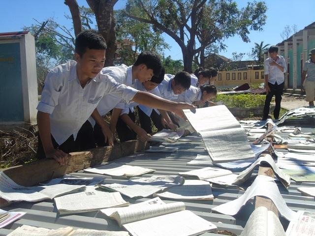 Giáo viên và học sinh Trường THCS Quảng Châu cố gắng gom nhặt dụng cụ thí nghiệm, sách vở còn sót lại