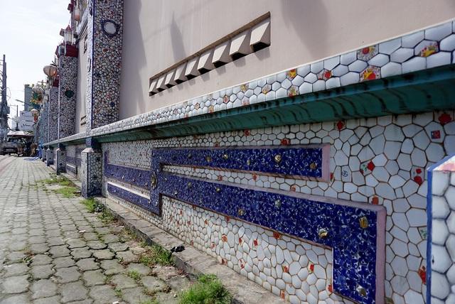 Bờ tường rào của ngôi chùa cũng được trang trí dày đặc mảnh sành sứ.