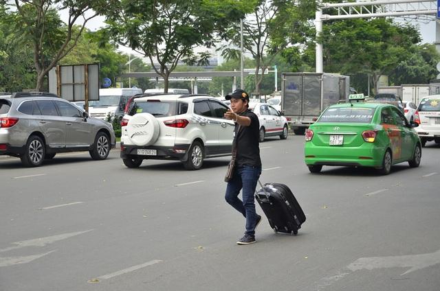 Nhiều người kéo vali đi bộ vào sân bay để kịp làm thủ tục lên chuyến bay