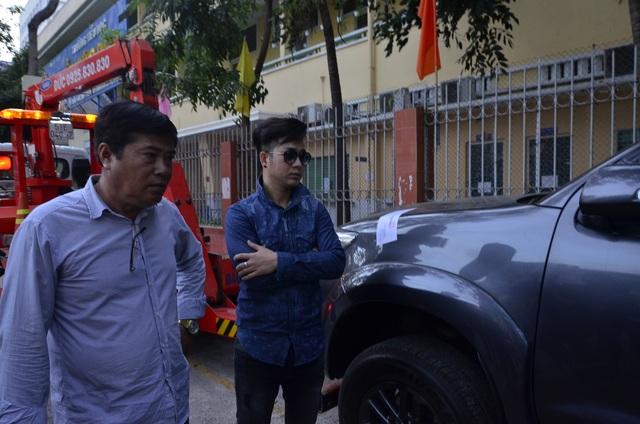 Nam ca sĩ Quách Tuấn Du bên chiếc xe bị cẩu đi.