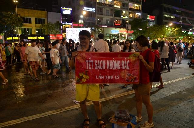 Nhóm tình nguyện SV07 với khẩu hiệu Tết sạch không rác trên đường hoa Nguyễn Huệ