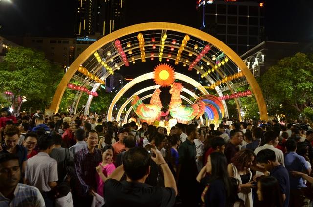 Người dân và du khách tập trung khá đông ở đầu đường hoa, nơi có gia đình gà, linh vật của năm Đinh Dậu