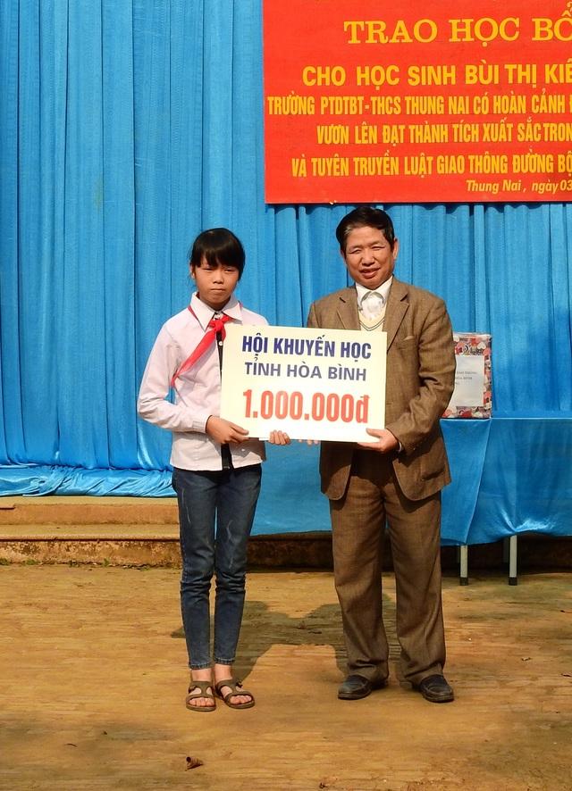 Ông Nguyễn Đức Hải - Ủy viên Thường vụ, Chánh VP Hội Khuyến học tỉnh Hòa Bình trao cho em Bùi Thị Kiều Trang một suất học bổng trị giá 1 triệu đồng