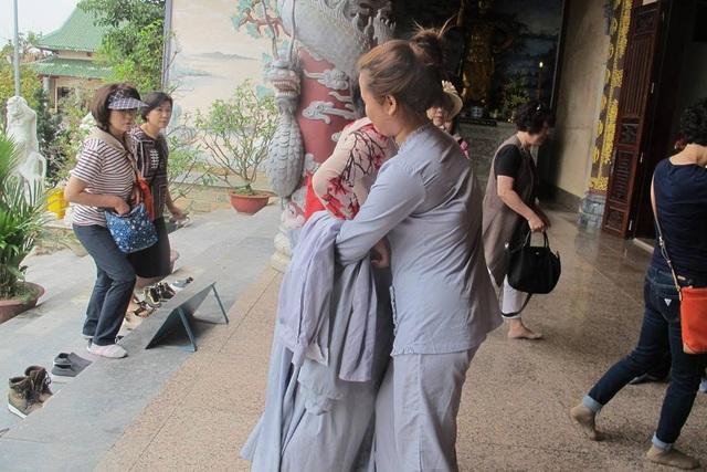 Du khách mặc váy ngắn, quần đùi khi vào chính điện của chùa để thắp hương sẽ được phát một chiếc váy choàng