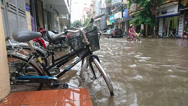 Vượt dòng nước ở phố Hoàng Văn Thái (Ảnh: Nguyễn Dương)