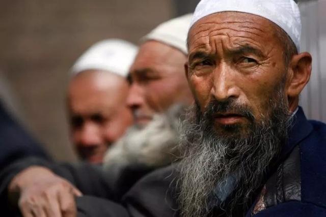 Những người đàn ông Duy Ngô Nhĩ ngồi chờ trước khi vào cầu nguyện bên trong thánh đường Hồi giáo ở Yarkand, Tân Cương (Ảnh: Reuters)