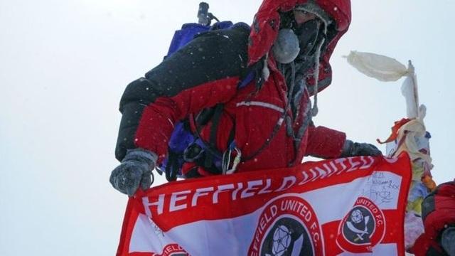 Anh cầm thêm lá cờ của đội bóng mình yêu thích - Sheffield United lên Nóc nhà thế giới