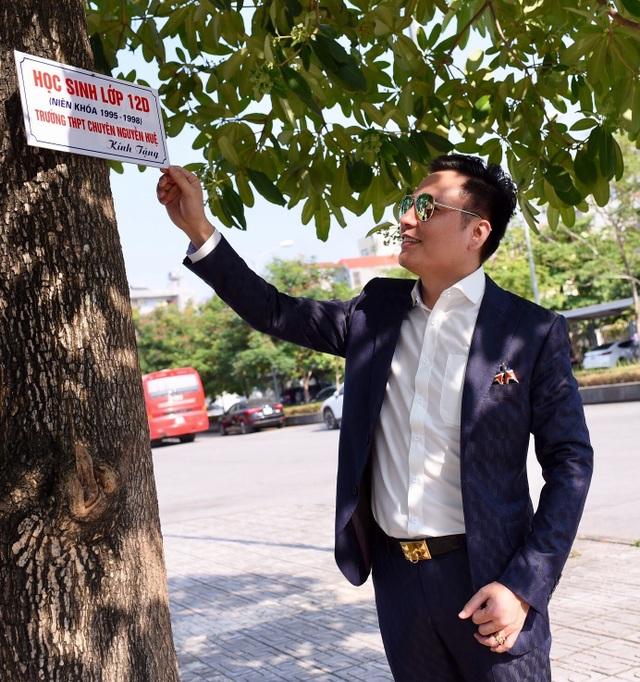 Đức Tuyên đứng cạnh cây mà tập thể lớp anh (lớp 12D niên khóa 1995-1998) kính tặng trường THPT chuyên Nguyễn Huệ