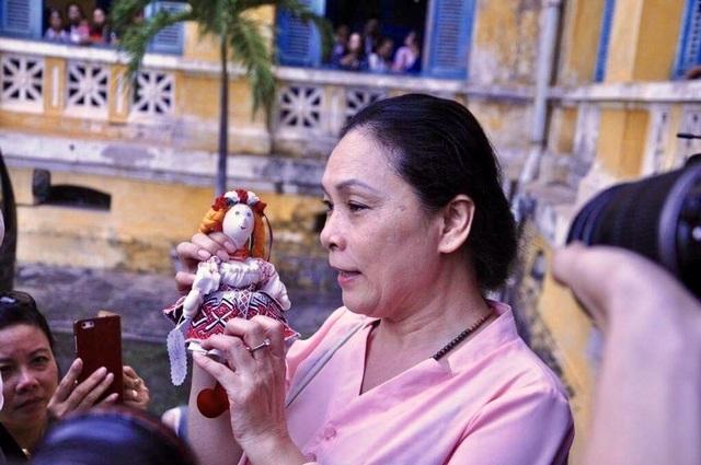 Bà Hồ Mai Phương (mẹ Phương Nga) đứng trước hành lang tòa chờ con gái. Bà cho biết tặng con gái mình búp bê may mắn.
