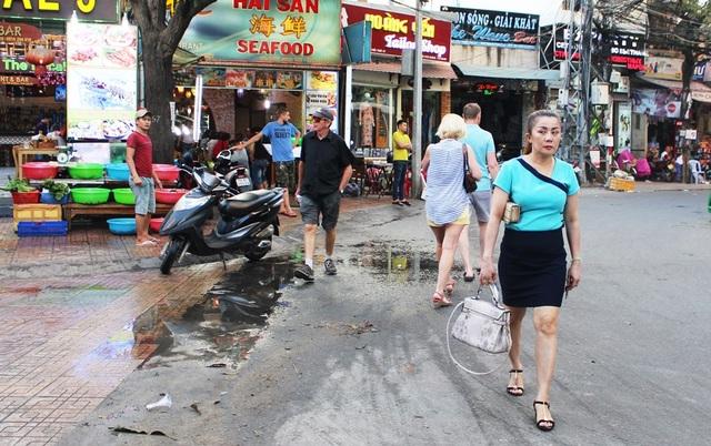 Chiều 9/3, theo quan sát của PV Dân trí, nhiều du khách nước ngoài trên các con đường được ví là phố Tây Nha Trang như: Hùng Vương, Nguyễn Thiện Thuật, Trần Quang Khải... bị đuổi xuống lòng đường vì việc tìm lối đi bộ trên vỉa hè với họ là khá chật vật