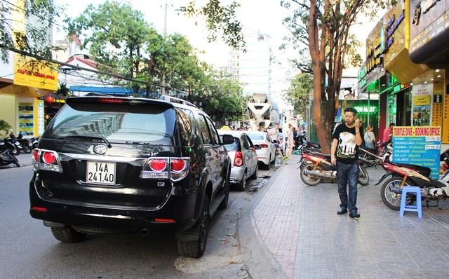 Trên đường Trần Quang Khải, du khách phải luồn lách vì ô tô dừng đậu kéo dài, còn vỉa hè thì bị một công trình xây dựng đang rào tôn ôm gọn