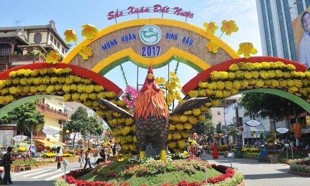 Cổng chính (đường Đại lộ Hòa Bình) vào đường hoa với biểu tượng chú gà trống vỗ cánh cất tiếng gáy...