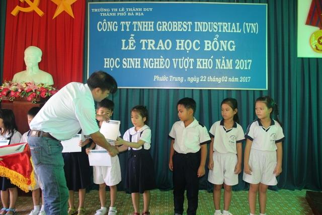 Ông Nguyễn Văn Dũng, giám đốc chi nhánh Công ty Grobest Việt Nam tại Bà Rịa - Vũng Tàu trao học bổng đến các em học sinh có hoàn cảnh khó khăn