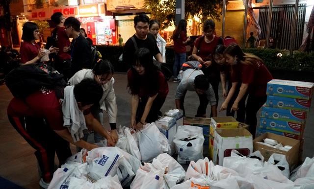 Các bạn sinh viên chuẩn bị các suất quà để phát cho những người vô gia cư. Mỗi phần quà gồm: áo ấm, dầu gió, sữa, bánh bao và bánh ngọt.