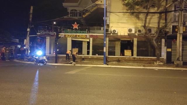 Nhân viên quán dọn dẹp mảnh kính vỡ văng ra đường sau vụ việc.