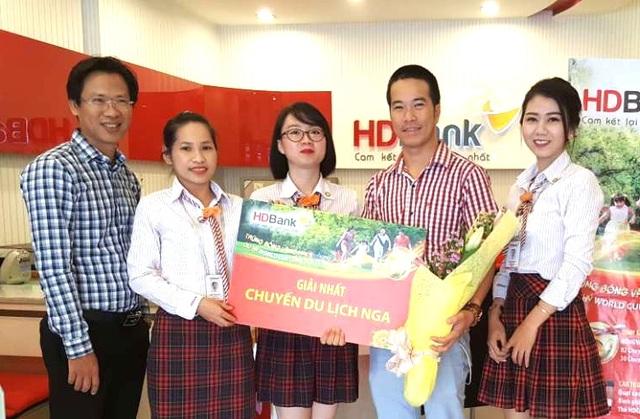 Khách hàng Bạch Minh Khoa (thứ hai từ phải sang) giao dịch tại HDBank Lê Quang Định (TP HCM) nhận giải nhất – chuyến du lịch xem WorldCup 2018 tại Nga trị giá 50 triệu đồng.