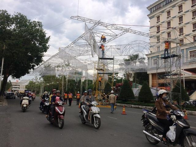 Các công nhân đang tất bật điều chỉnh hệ thống đèn trên đường Hòa Bình (TP Cần Thơ) để kịp mừng Giáng sinh và tết dương lịch