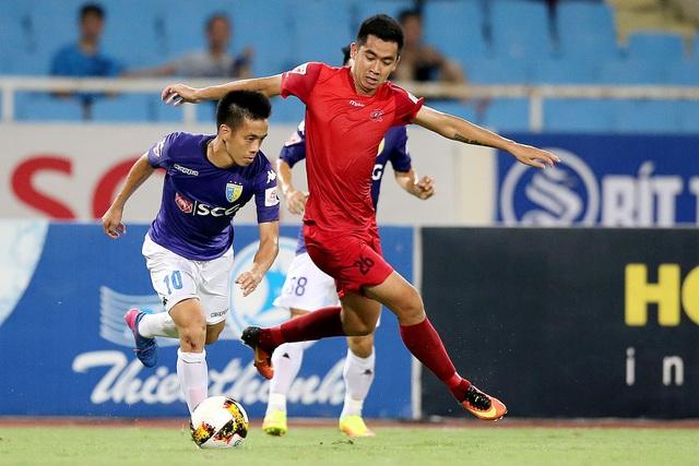 Văn Quyết (FC Hà Nội, trái) đi bóng trước sự truy cản của cầu thủ Hải Phòng (phải), ảnh: Minh Phương