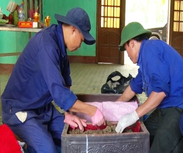 Đội tìm kiếm, quy tập, cất bốc hài cốt (Đội 584) cẩn trọng đưa các mẫu xương, di vật vào tiểu sành (Ảnh: Ph.Q.)