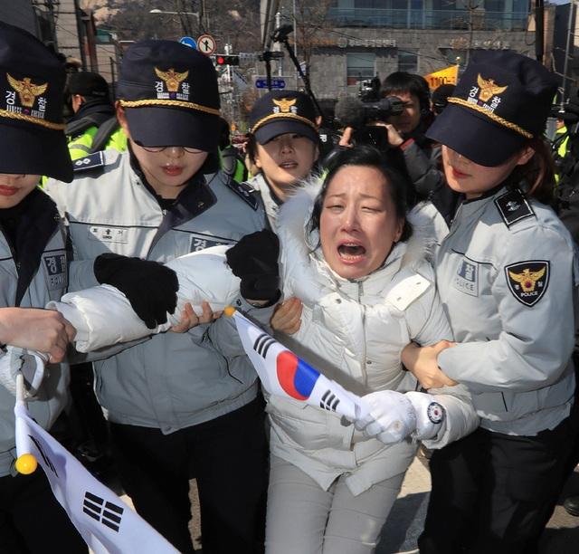 Một người ủng hộ bà Park khóc trong bị cảnh sát giải đi. (Ảnh: AFP)