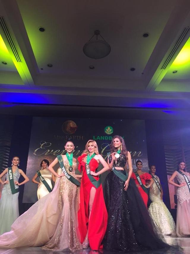 Hà Thu (trái) giành huy chương đồng phần thi Trình diễn trang phục dạ hội tại Hoa hậu Trái đất 2017, tối 22/10.