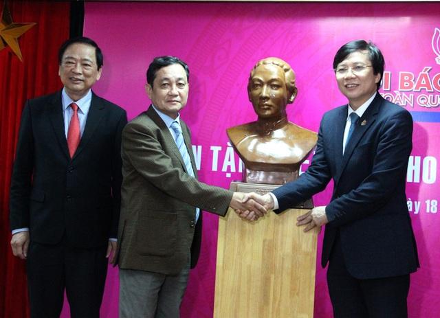 Nhà báo Hồ Quang Lợi (bìa phải) tiếp nhận bức tượng về nữ chủ bút báo đầu tiên của Việt Nam - bà Sương Nguyệt Anh.