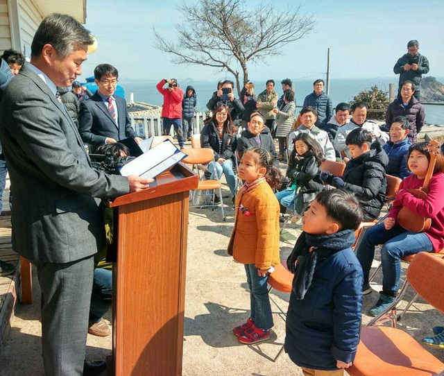 Hiệu trưởng Trường tiểu học Cheongpa, ông Lee Min-cheol, trao giấy nhập học cho cậu bé Ryu Chan-hee (bên phải) và cho một cô bé khác vào học điểm trường khác trên đảo Hodo tại buổi lễ nhập học ngày 3/3/2017. (Ảnh: Hankook Ilbo)