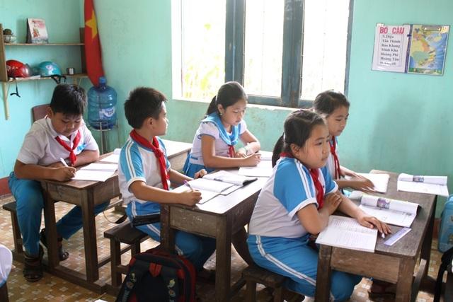 Học sinh lớp 4 trường TH thị trấn Sông Vệ chật vật với cỡ bàn ghế dành cho học sinh lớp 1.