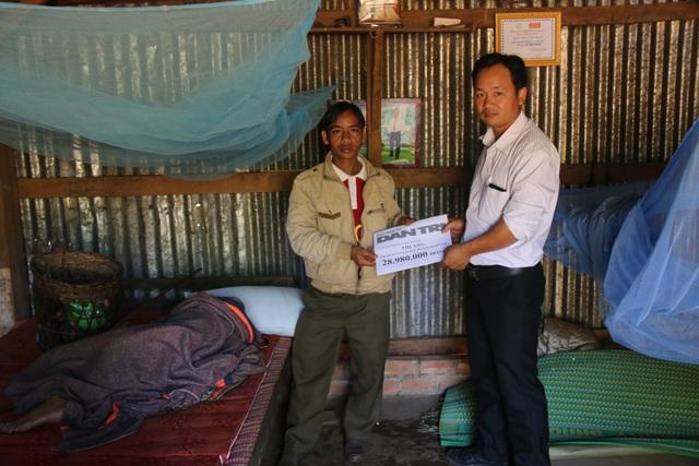 Đại diện chính quyền địa phương trao tiền cho anh Điểu Hoang, người được cử chăm sóc và quản lý vật chất cho cụ Thị Ang
