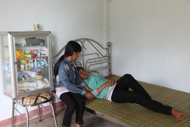Phòng y tế sơ sài với một chiếc giường đơn và một tủ thuốc y tế