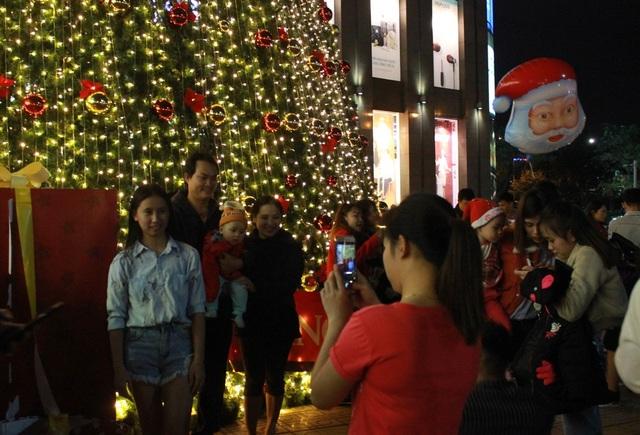 Tại Trung tâm thương mại, cây thông trang trí bằng đèn nháy cao hơn 20 mét là nơi nhiều gia đình, nhiều bạn trẻ đến vui chơi, lưu lại những khoảnh khắc đáng nhớ.